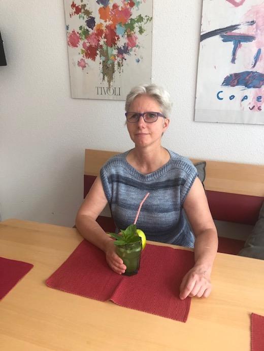 Claudia trinkt Ligumi-Cocktail. Im glas befindet sich ein Strohhalm sowie ein Minzzweig. Am Glasrand steckt eine Limette