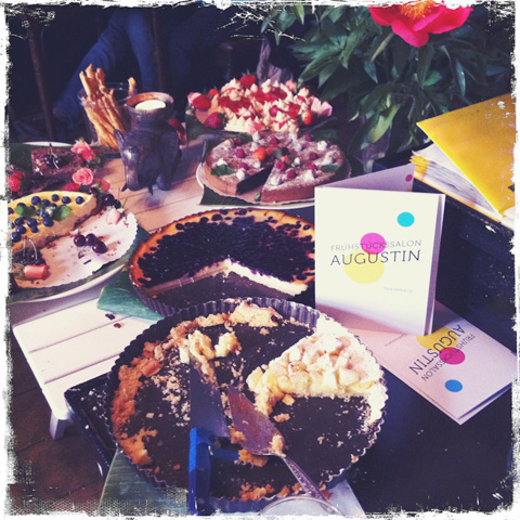 Das Augustin, Innenbereich mit Tisch, verschiedene, aufgeschnittene Kuchen und Frühstückskarte