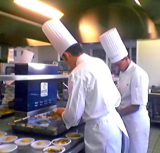 Köche beim Kochen in einer modernen Großküche