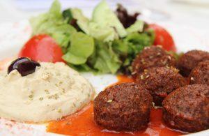 Teller mit Falafel, Tomatensauce, Humus und Salat