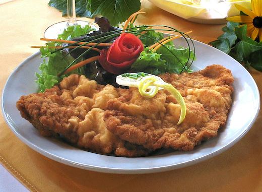 Wiener Schnitzel mit Zitronenscheibe und Salat sowie eine Rose als Dekoration
